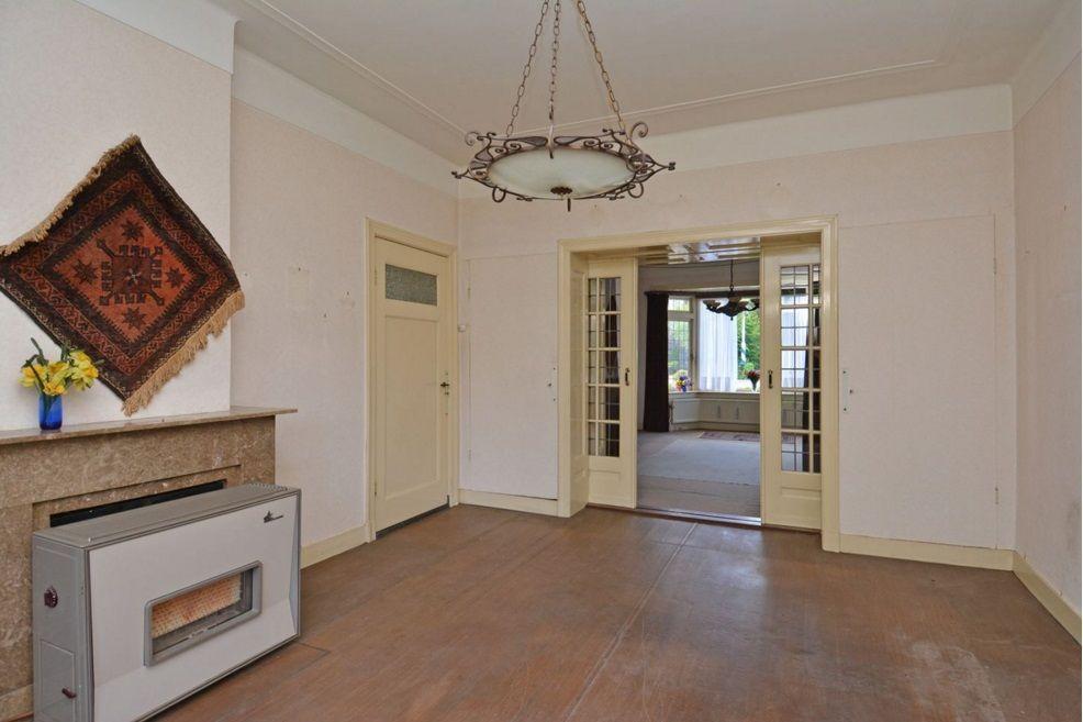 1935 woonkamer hoge plinten, paneeldeur naar gang, plafond en lamp ...