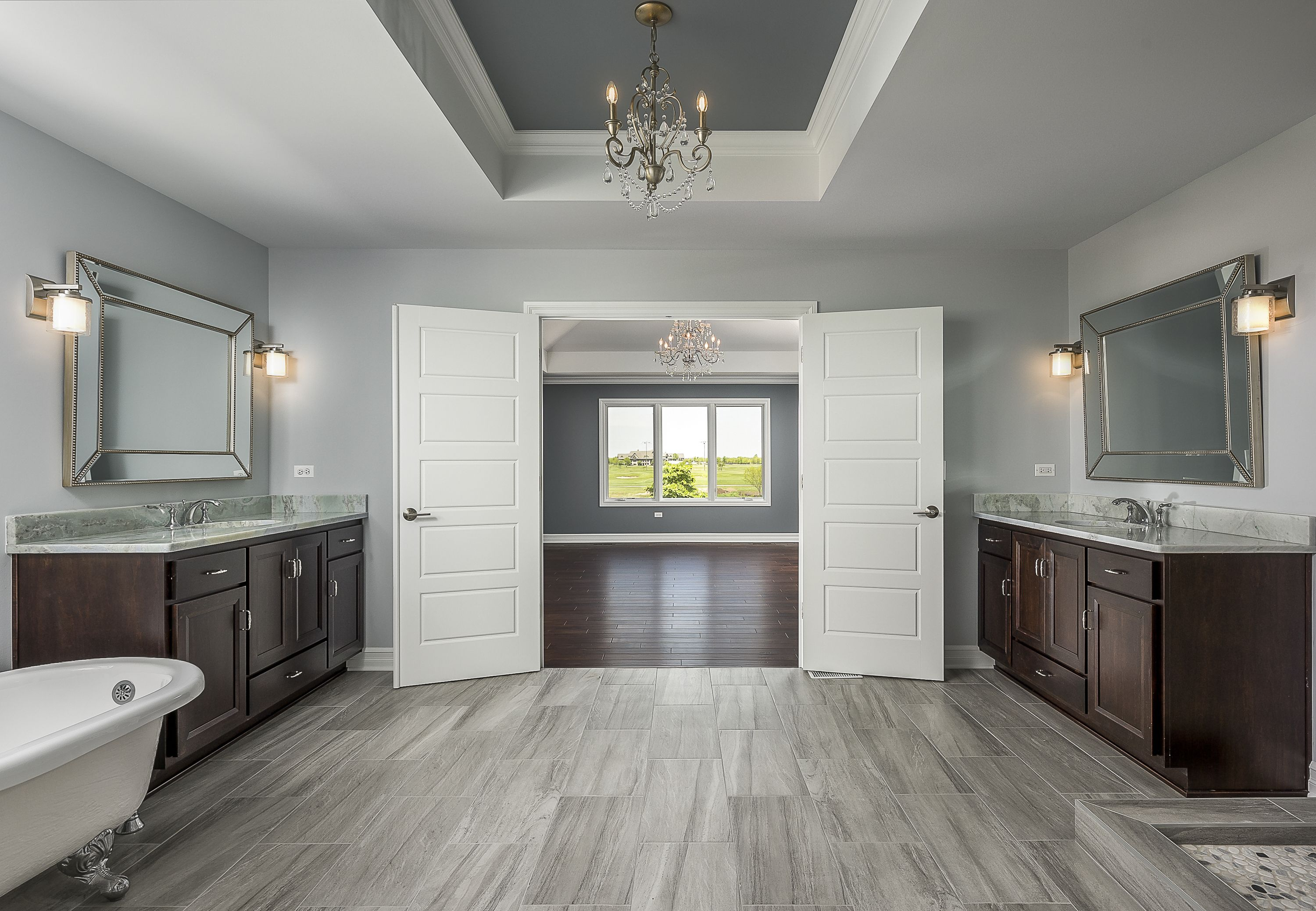 Custom Home Master Bath With Beautiful Double Door Entry Chandelier Freestanding Tub And Separate Vanities Custom Homes House Tiles Home