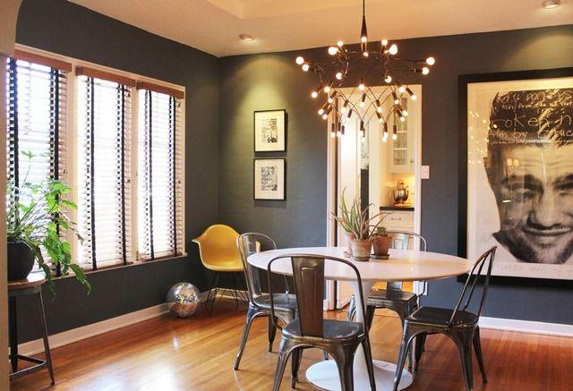 Saarinen table, industrial chairs, dark walls, crisp white door trim and baseboard.