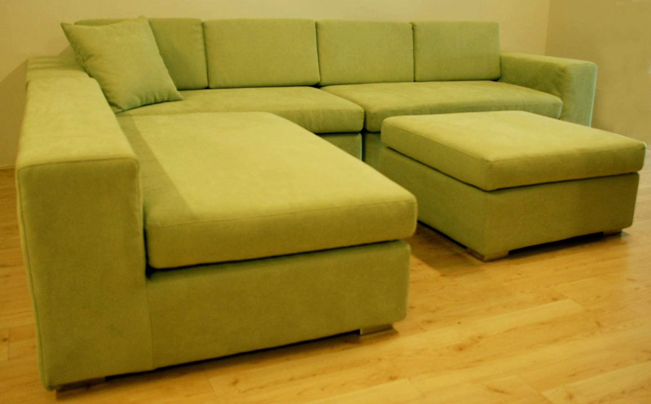 Charming L Shaped Green Leather Sofa With Track Arms And Padded Seat Cushion