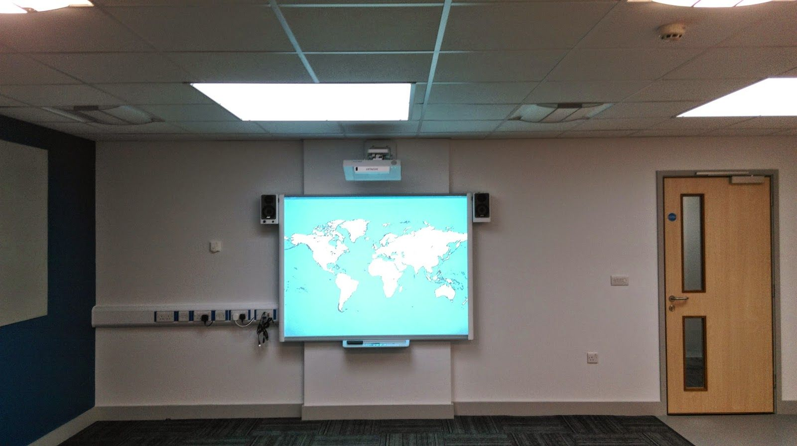 A Hitachi Ultrashort Throw Projector Mounted To The Wall Above An Interactive Smart Board Projector Setup Projector Mount Projector