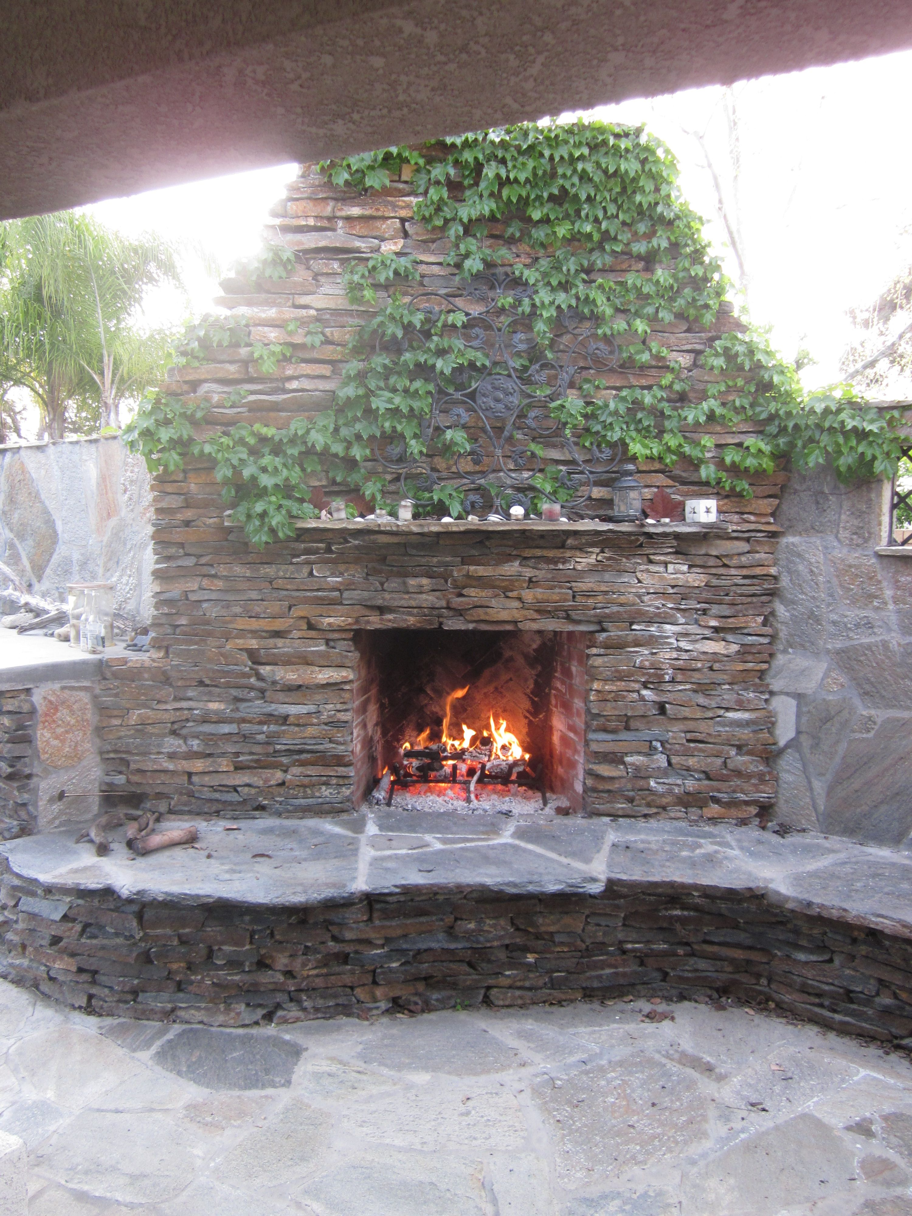 Stacked Rock Fireplace With Ivy Outdoor Stone Fireplaces Backyard Outdoor Fireplace