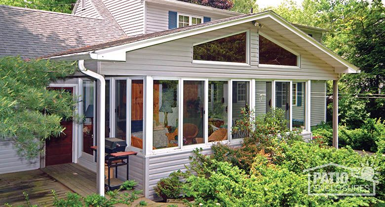 Traditional Sunroom With Glass Wings Under A Shingled Gable Roof