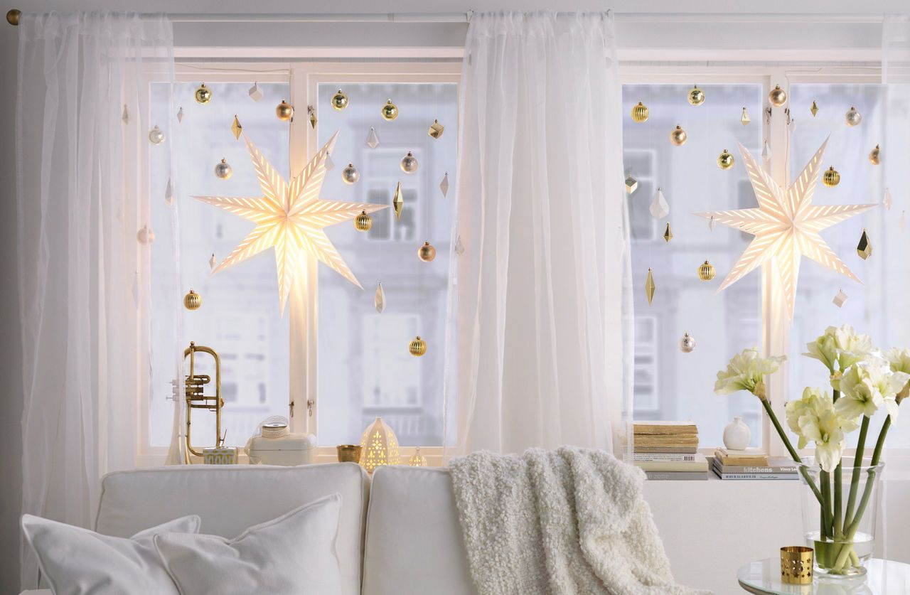 A white sofa in front of a window decorated with hanging white and ...