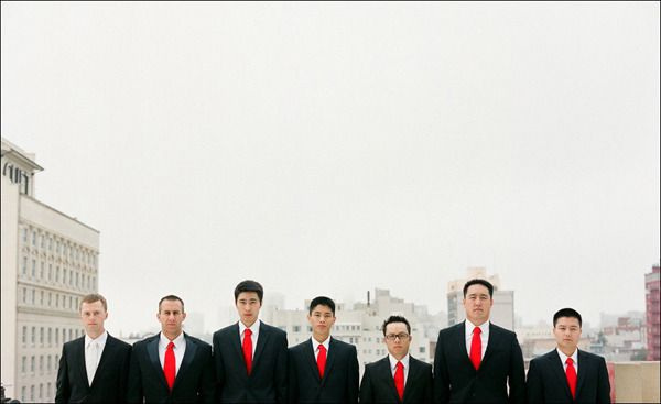 groomsmen smart in suit matched with red tie.