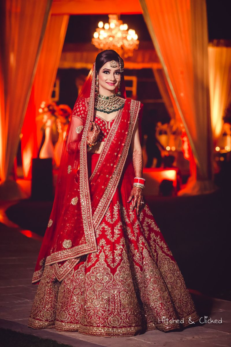 Red bridal lehenga with green jewellery Indian wedding