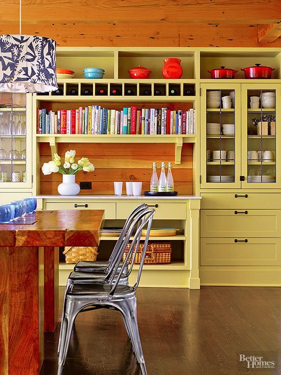 Nothing highlights a unique piece like color. Painted in effervescent green, this wall of open and closed cabinetry becomes a focal point of the kitchen and shows off a china collection to stellar effect.