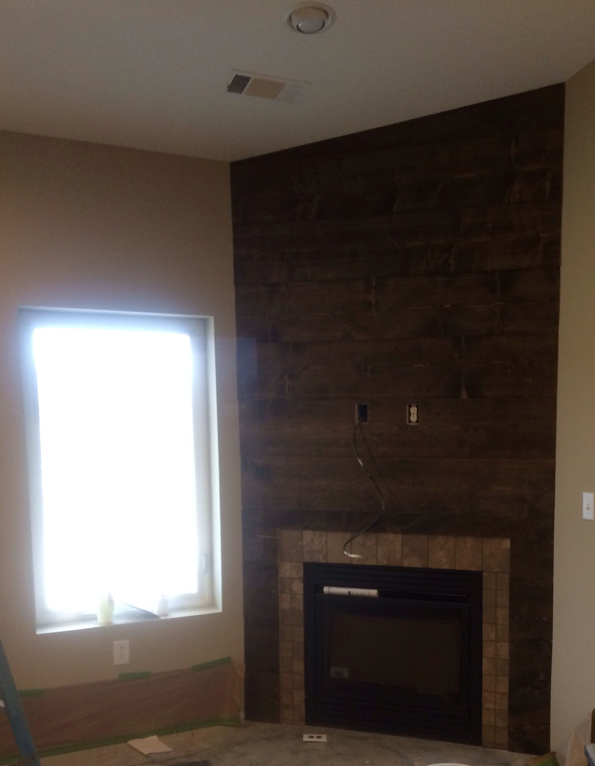 Shiplap Corner Fireplace With A Stone Border Around The