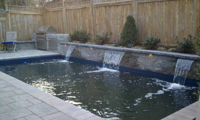 Traditional Rectangular Pool With Water Features Shooting Into The
