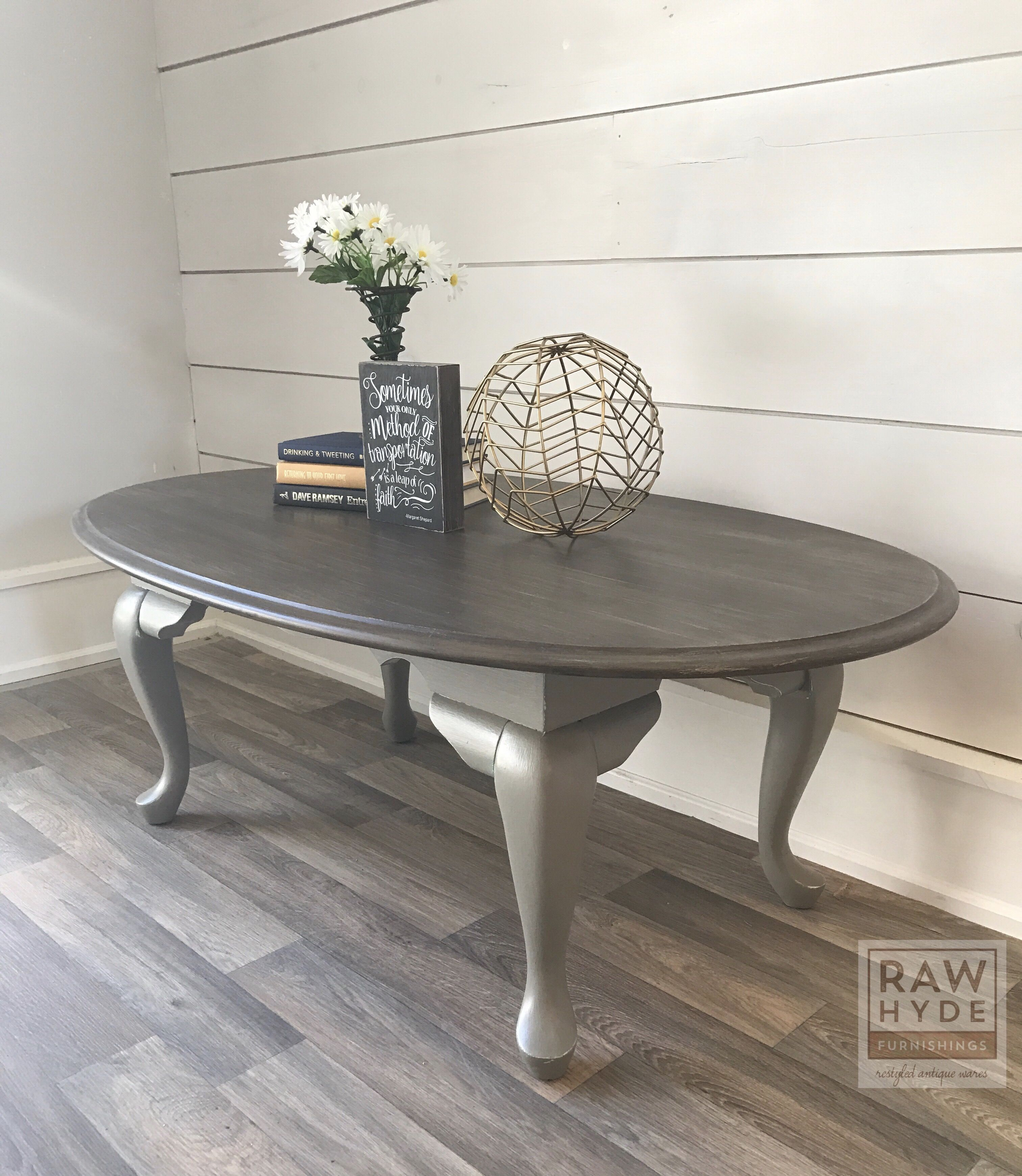 An Oval Table Takes On A Farmhouse Style Look With A Distressed Weathered Wood Finish Wood Furniture Design Distressed Coffee Table Home Decor