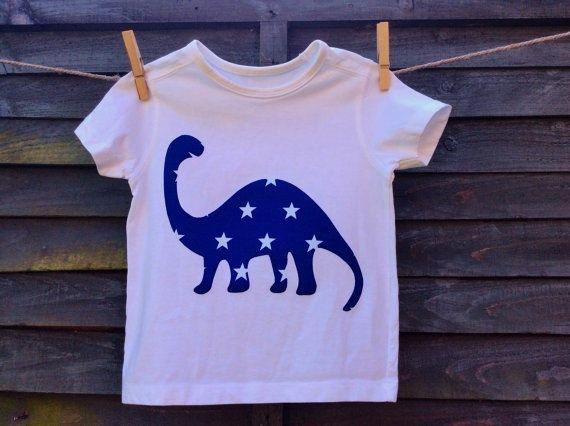 Dinosaure blanc du garçon t-shirt, chemise en coton 100 % avec un dinosaure diplodocus de bleu étoilé appliqués impression.  Le diplodocus est confectionné dans une étoffe de coton bleu avec des étoiles blanches. Il a été fusionné au t-shirt puis machine cousu sur lutilisation dun point de droit et souligné pour le confort.  Sur le dos du T-shirt est le logo de Hugstar en violet avec une étoile jaune, sérigraphié à laide dencre solvant tissu gratuit.  Prérétréci et maintient une grande forme…