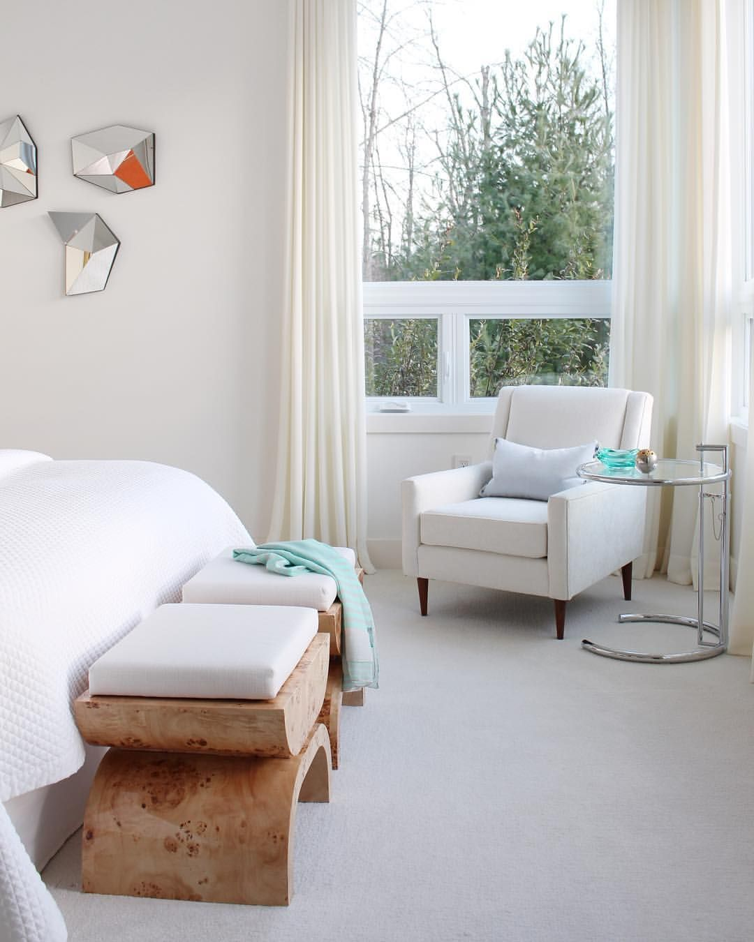 All white bedroom with solid wood benches at the