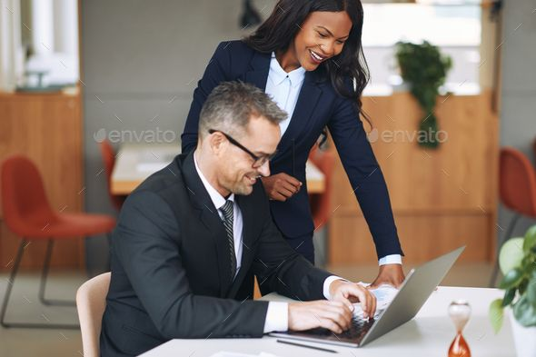 Two smiling diverse businesspeople working together on a laptop by FlamingoImages. Two smiling diverse businesspeople talking together while working on a laptop at a table in an office #AD #businesspeople, #working, #smiling, #diverse