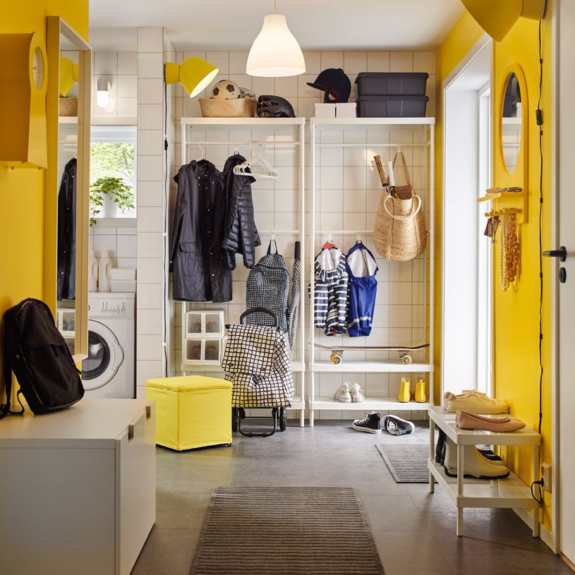 A bright yellow and white mudroom with a white coat and shoe rack ...