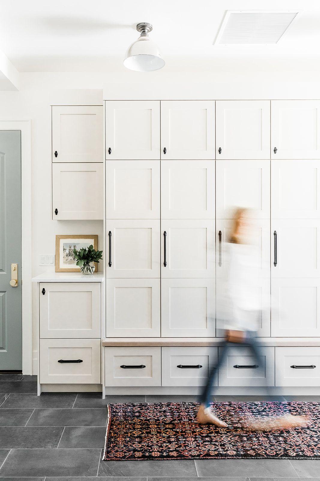 White Mud Room Built Ins Vintage Rug Slate Tile Floors Black Hardware Subtle Natural Wood Elements And Gold Design