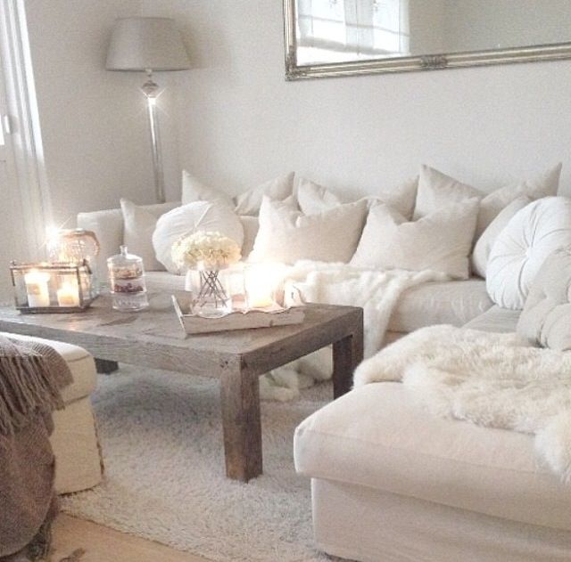 Cozy Living Room With Lamp Behind Couch In Corner And Wooden Table White Candles
