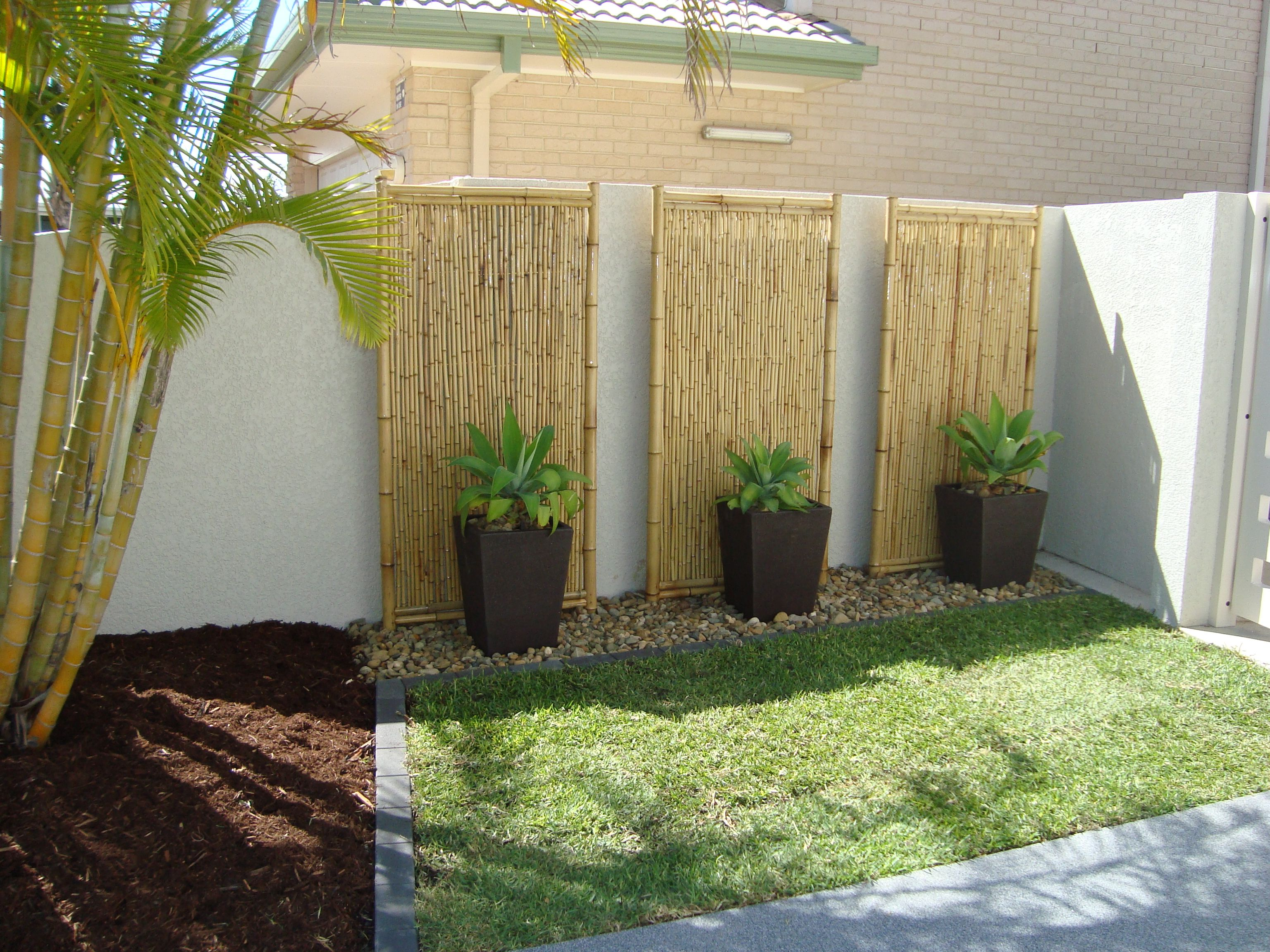 Tall planters and rocks against wall lined by stones for Small front yard ideas with fence