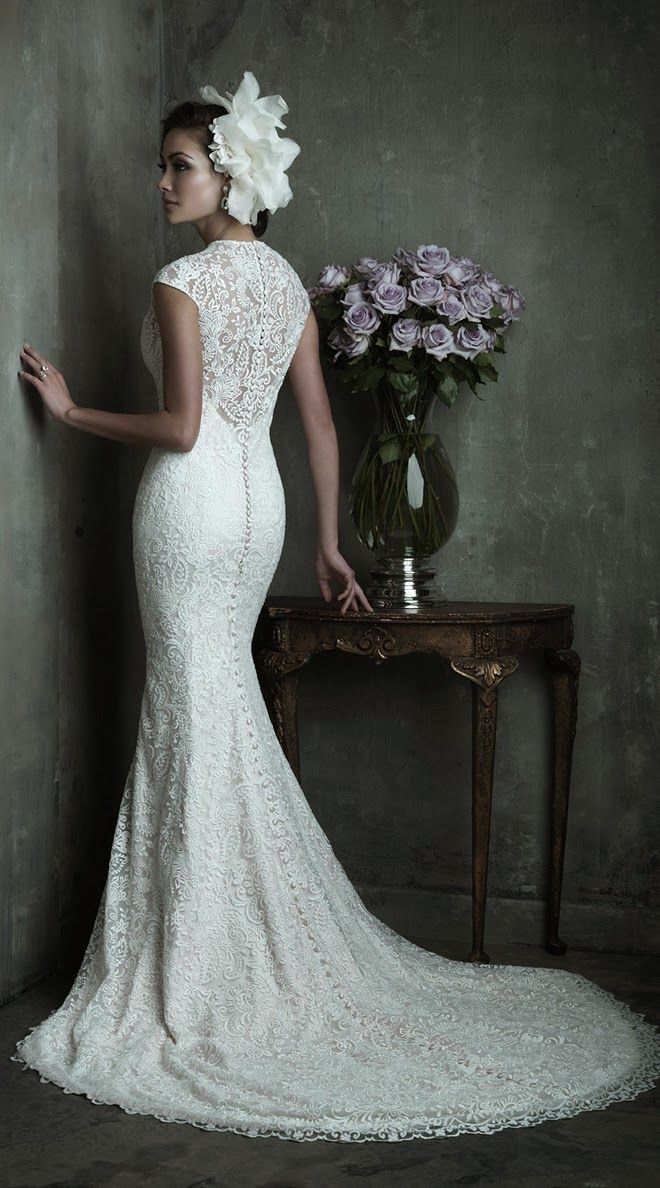 This sophisticated lace wedding dress consists of a slim-fitting charmeuse slip and lace overdress. A high neckline and slight cap sleeves add an extra measure of elegance to the already graceful silhouette.