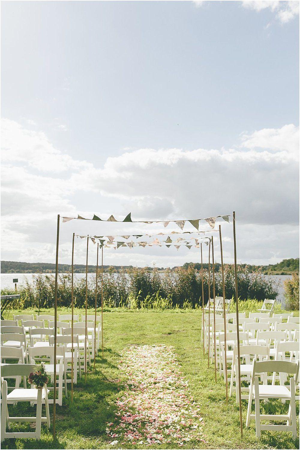 Blumenweg Durchgang Trauung mit Wimpelketten. Hochzeit am Wasser, Von Anmut und Sinn. Foto: Lene Photography