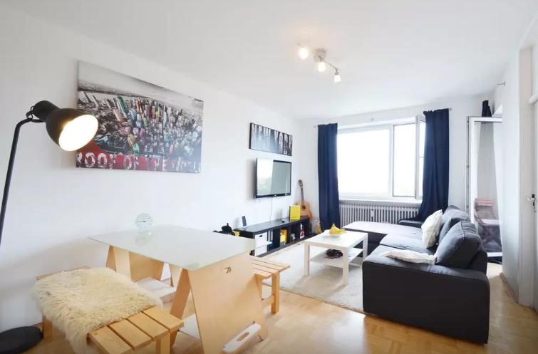 Modernes Wohnzimmer Mit Großer Couch, Fensterfront Und Sitzgelegenheit In  München. Wohnen In München. #München #Wohnung #Wohnzimmer #livingroom