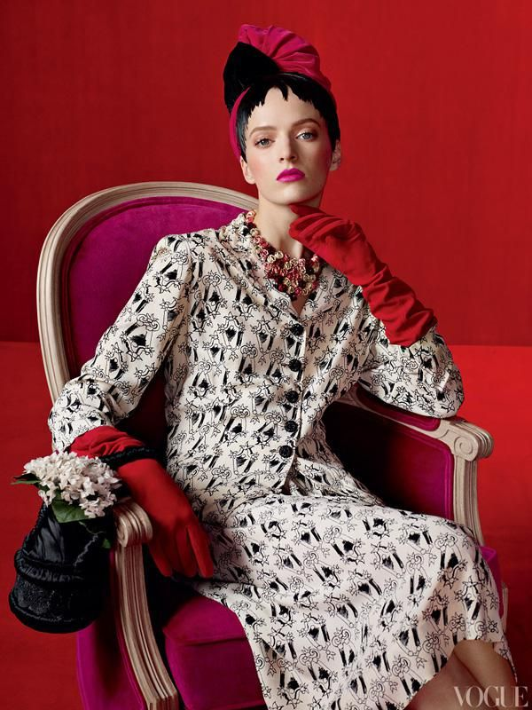 Model Daria Strokous wears Schiaparelli's Mirror Print suit with flower buttons (spring 1937), silk-velvet turban (winter 1937-38), rose necklace of enameled gilt metal and flower vase silk-satin purse beaded by Lesage (both 1938), and Portolano gloves.