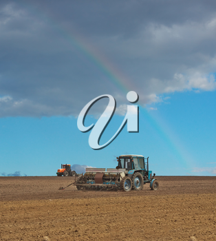 Tractor sowing the field with the seeder and a rainbow in the sky