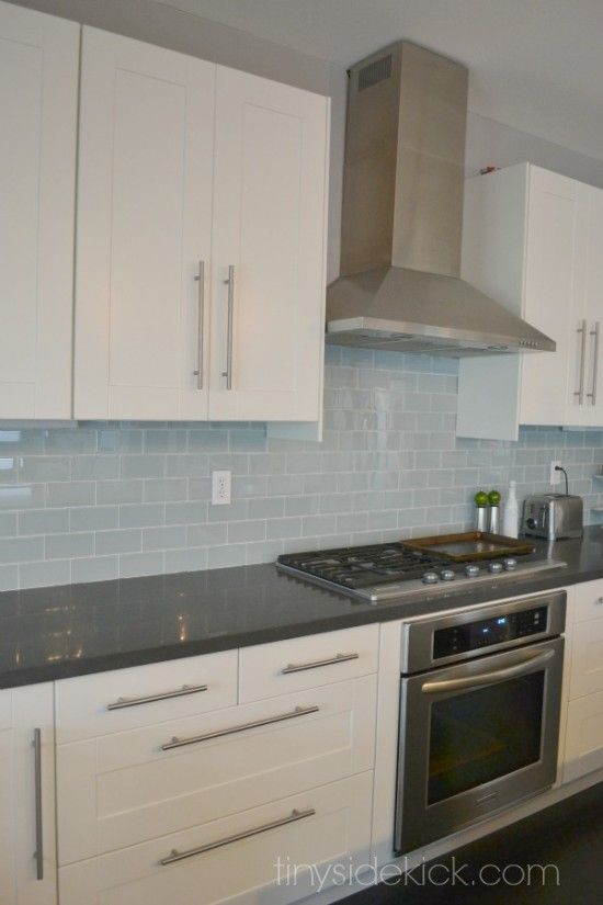 Dark Grey Countertop And Light Blue Backsplash With White Cabinets