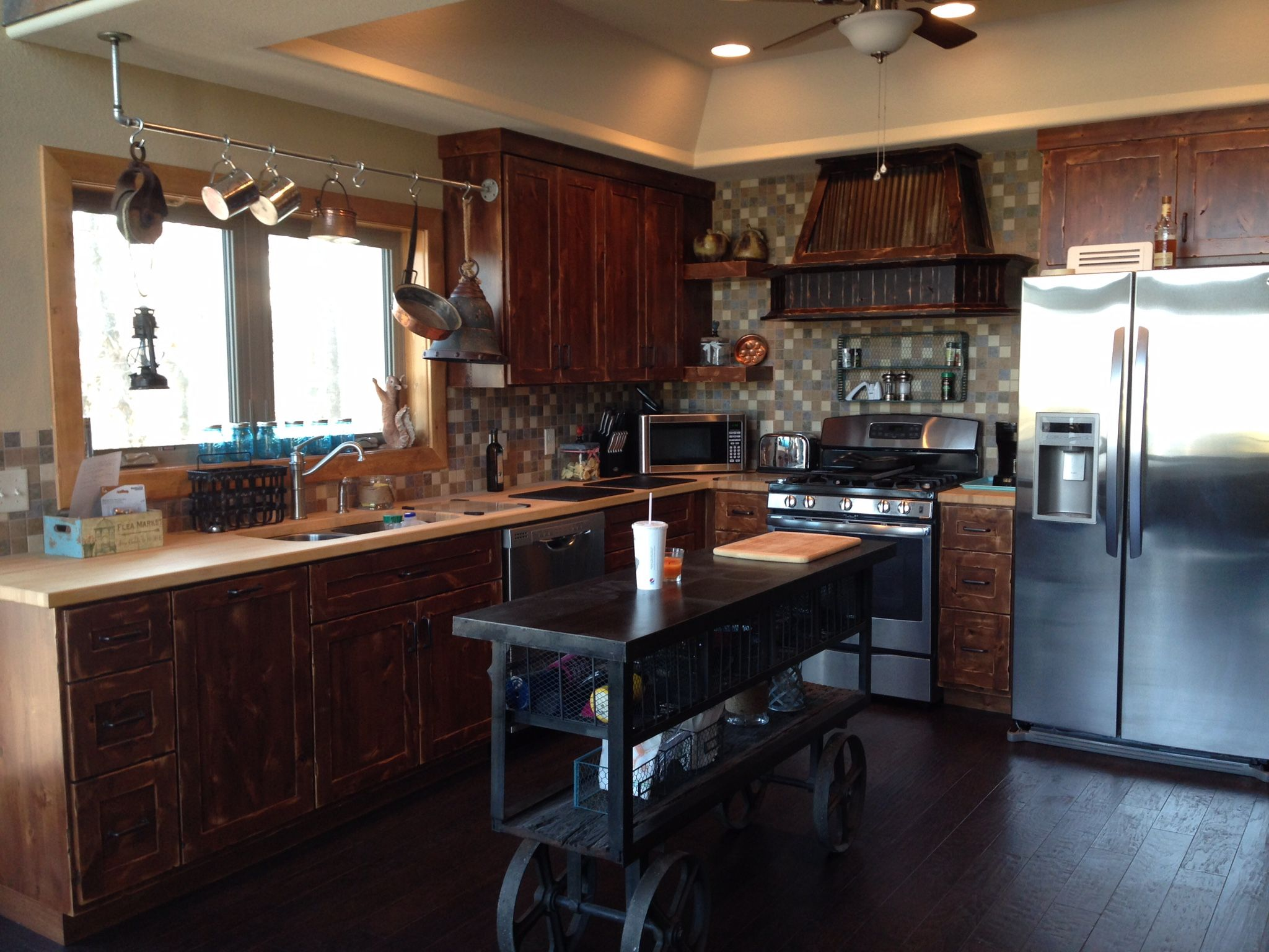 Rustic kitchen cabinets with a butcher block counter. Trolley cart on