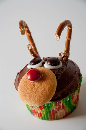 adorable reindeer cupcakes! i've made these they're super easy. white and red mn'ms. but use mini vanilla wafers. black decorator tube frosting/gel. fudge choco frosting or nothing will stick. and pretzl's cut in half. make sure you allow the cupcake to cool prior to frosting it.