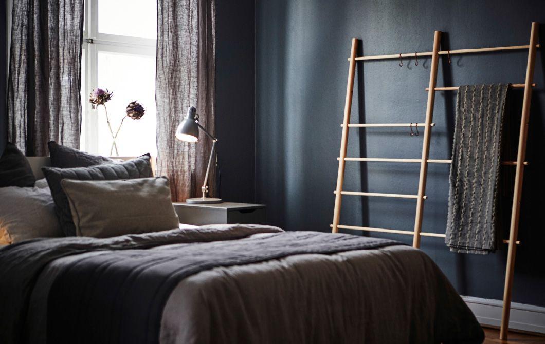 Ein Schlafzimmer mit dunklen Wänden, darin ein Bett, ein
