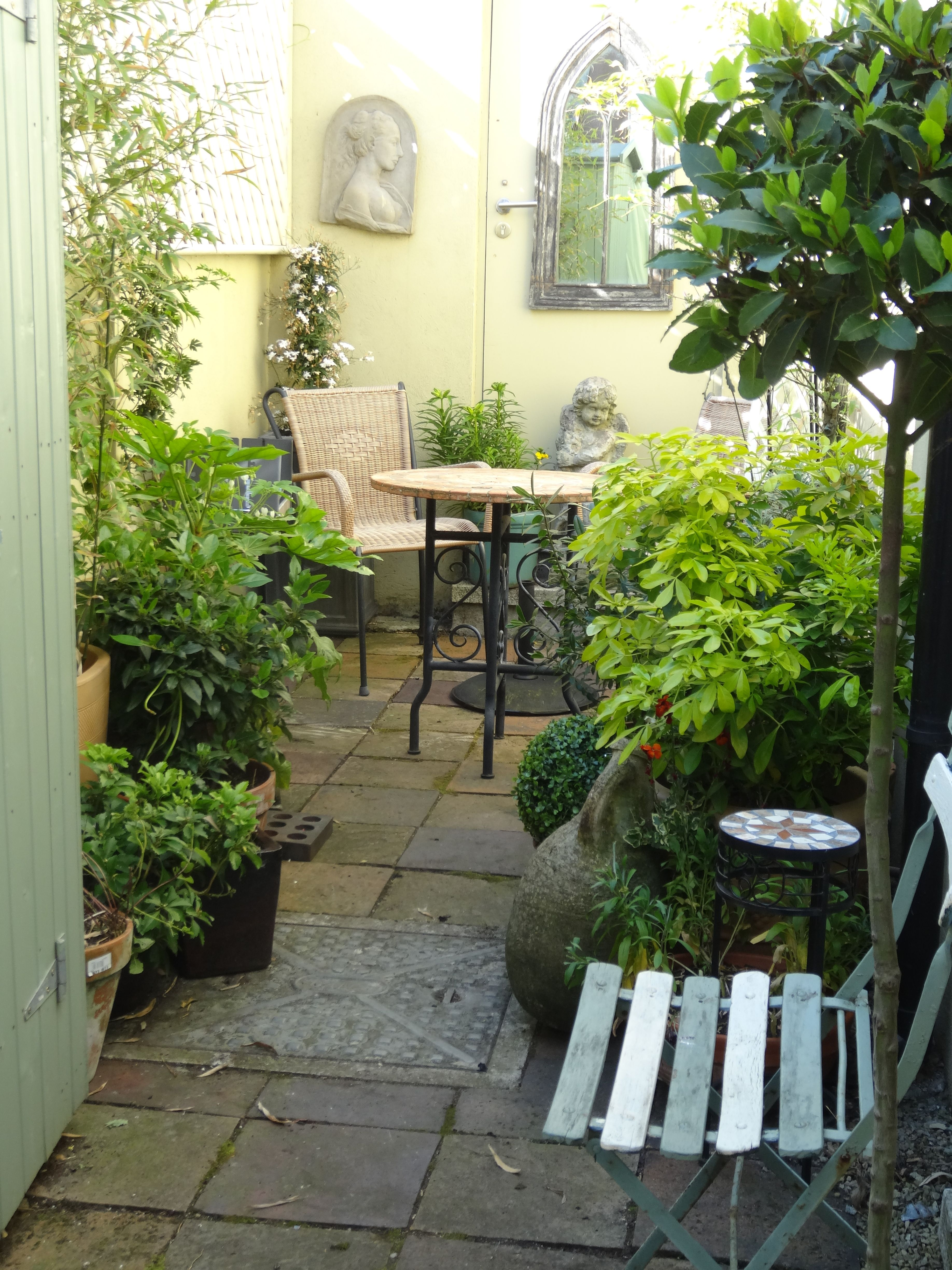 make the most of a tiny city courtyard with tall lush plants and small furniture