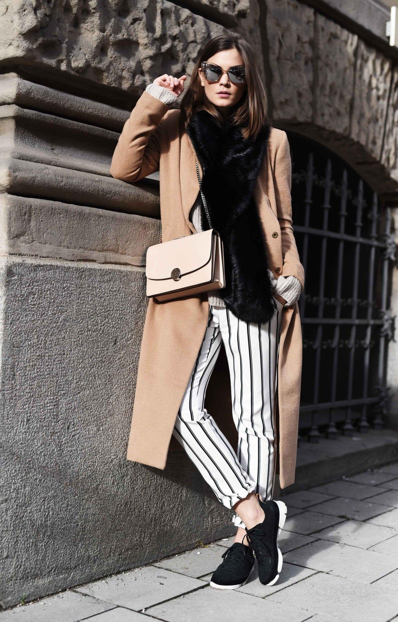Nina Schwichtenberg trägt eine gestreifte Hose, dazu kombiniert Sweater,  Jacke und Tasche in Brauntönen