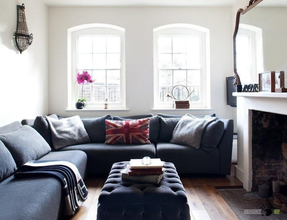 Cozy gray sofa with pillows and blanket along with tufted table