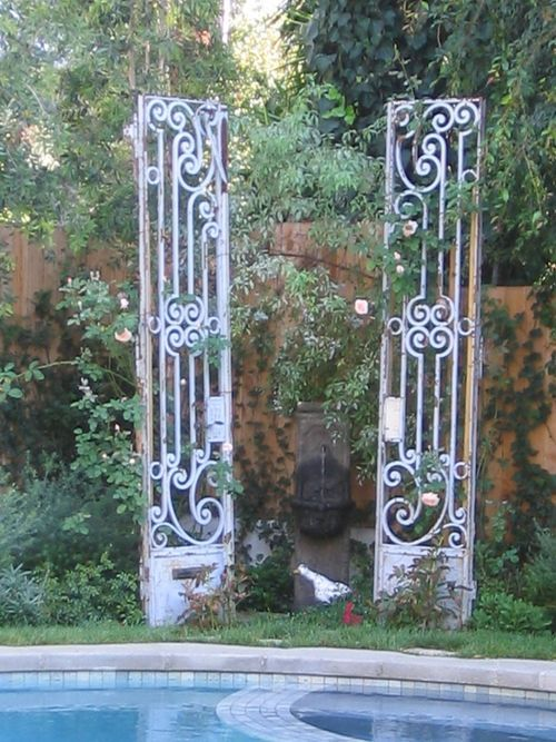 Old iron gates and a fountain make a great focal point at the back of a garden