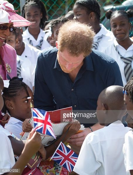 Akia Slocombe shows Prince Harry a picture of her father Tim who was injured while serving in Afghanistan during his visit to a community sports park on his 9-day visit to The Carribean. Nov. 28, 2016