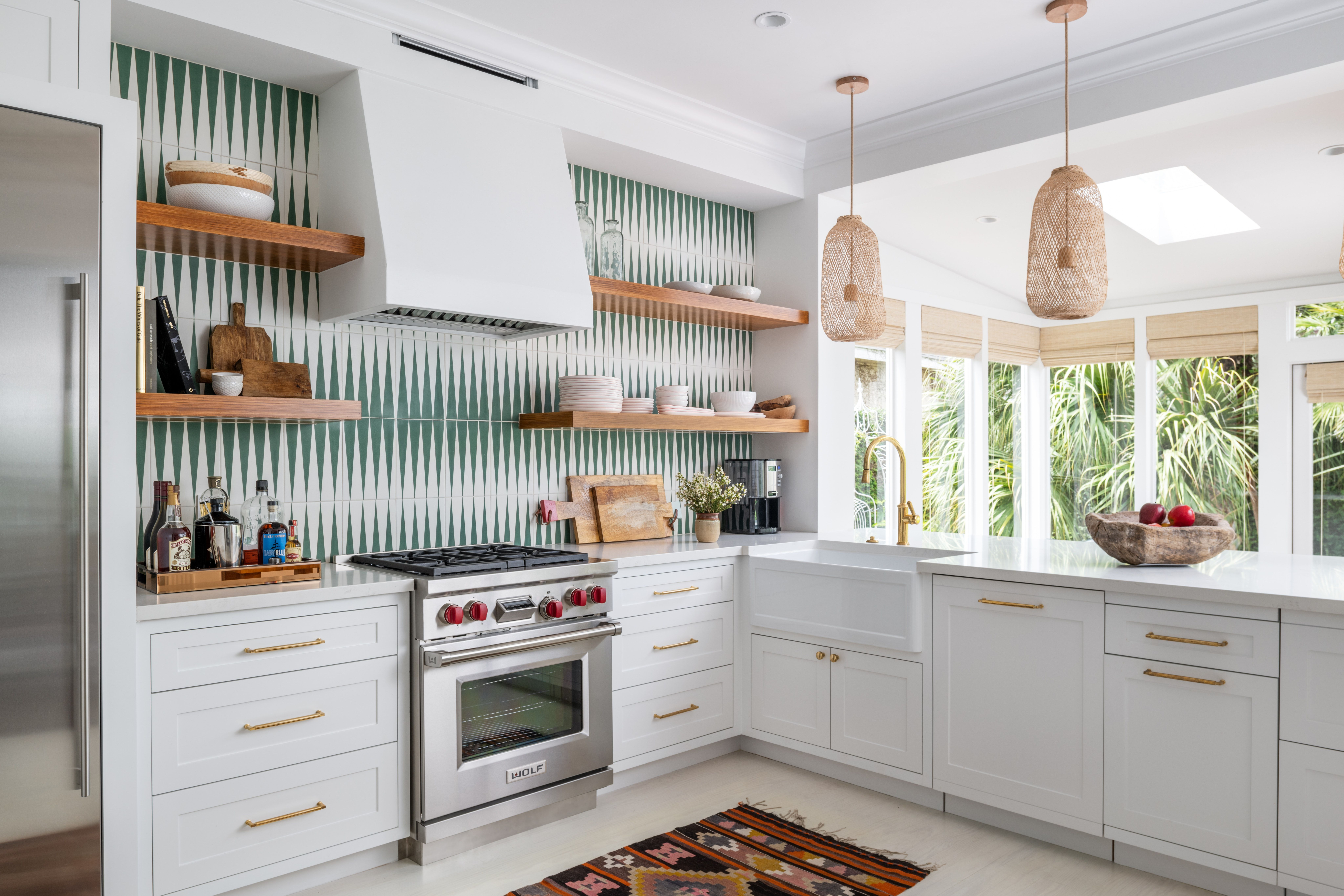 A Bright Kitchen With Open Shelving And Green Patterned Tiles By