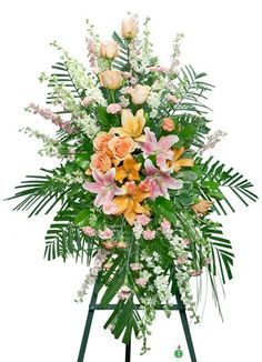 Share the spirit of hope and faith with a generous standing spray of pink and orange blossoms including lilies, roses, and carnations against a backdrop of fresh palm fronds. A lovely way to express y