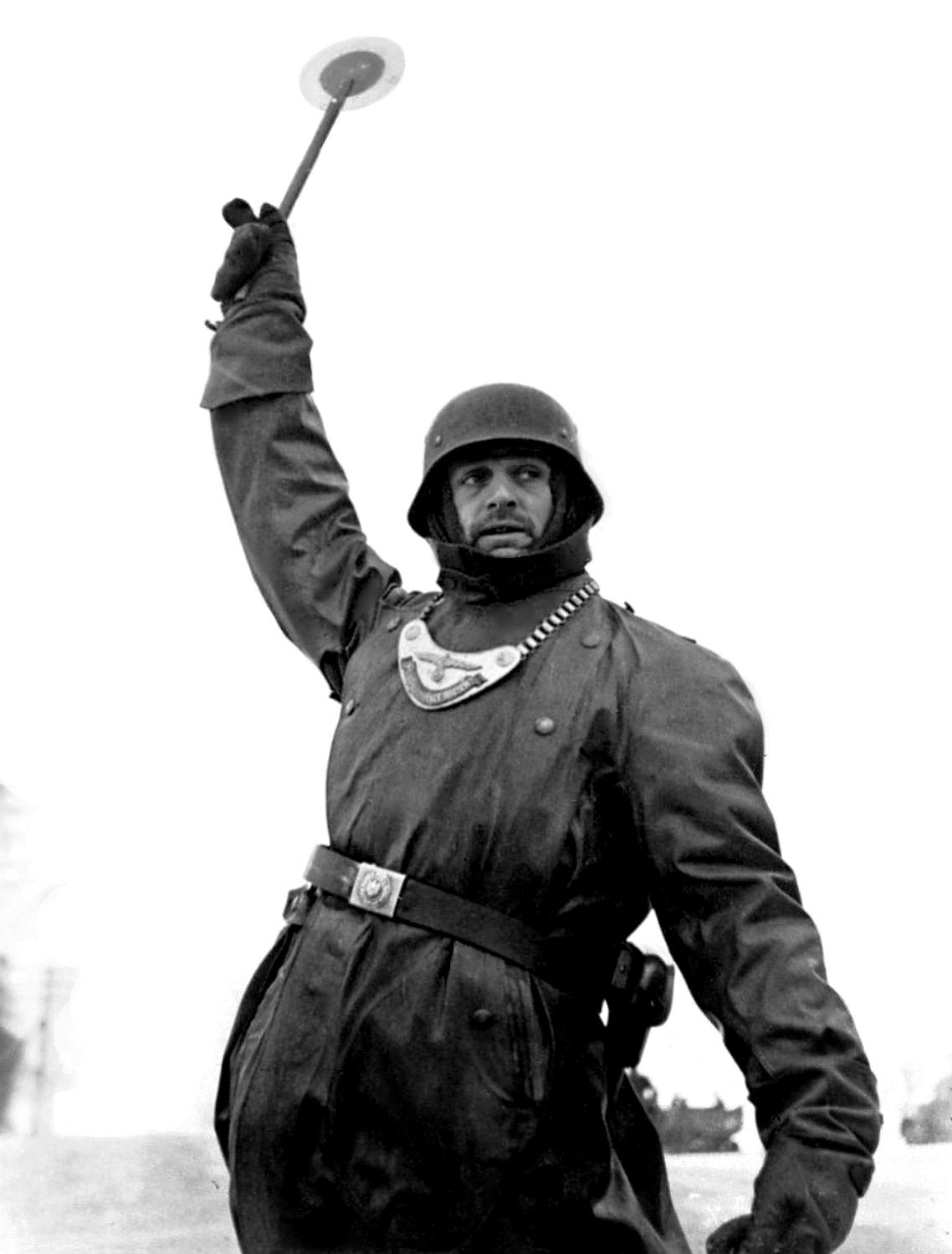 A German Wehrmacht soldier of the Feldgendarmerie (military police) directs military transport during the Battle of Moscow. Feldgendarmerie units were generally given occupation duties in territories directly under the control of the Wehrmacht. Their duties policing the areas behind the front lines ranged from straightforward traffic and population control to suppression and execution of partisans and the apprehension of enemy stragglers. Moscow Oblast, Russia, Soviet Union. December 1941.