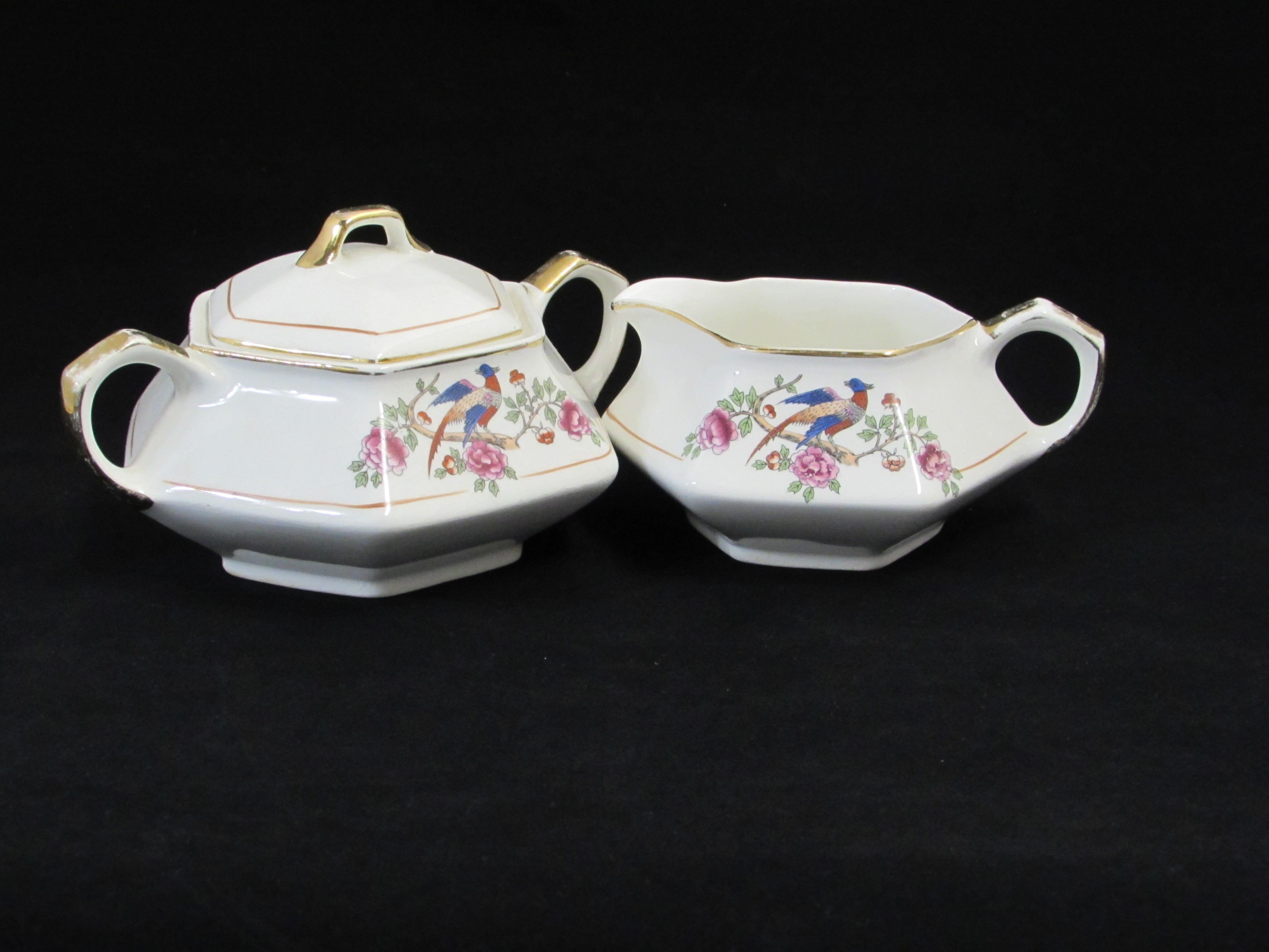 """F.C. Co. Martha Washington Creamer and Sugar. This sugar and creamer set is in the Martha Washington pattern. It features a pheasant on a tree branch. F.C. Co dates to around the late 1800's to the early 1900's. This set does have a lot of wear and crazing. The creamer is approx. 5 1/4"""" from spout to handle and stands approx. 2 1/2"""" tall. The sugar is approx. 3 1/2"""" tall x 7"""" across the handles. The set is in good condition with no chips or cracks. There is crazing present and wear…"""