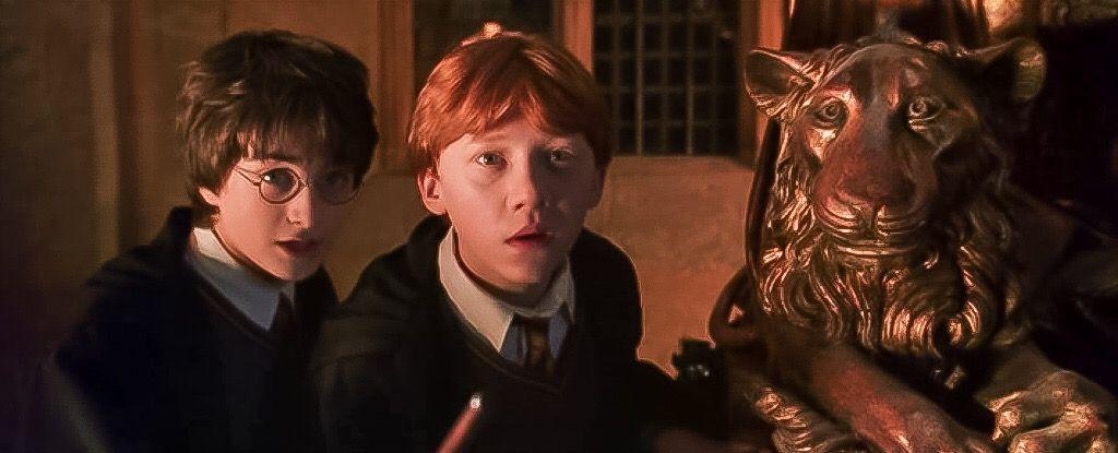 Harry a Ron se schovávají za sochou se lvem a dívají se dopředu. Scéna z filmu Harry Potter a Tajemná komnata. Oba chlapci čekají na Crabbeho a Goylea, na které nastražili mufínky s bonusovou ingrediencí navíc.