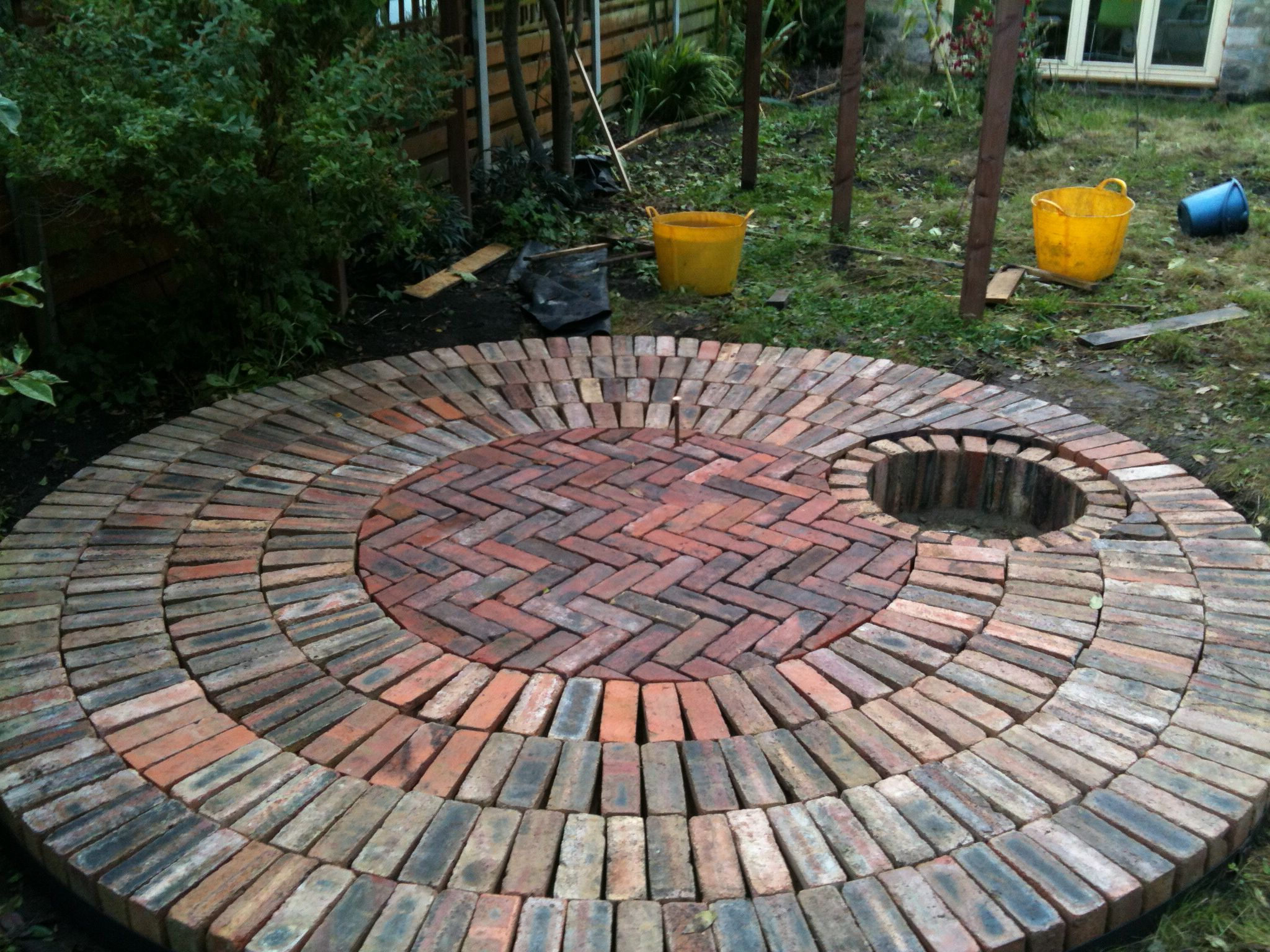 circular reclaimed brick patio with recessed fire pit