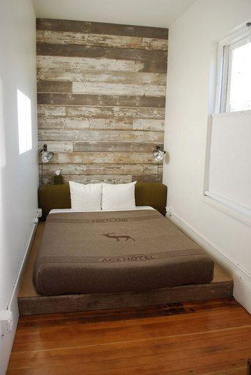 um quarto que é só a cama; gostei da parede do fundo revestida de madeira.