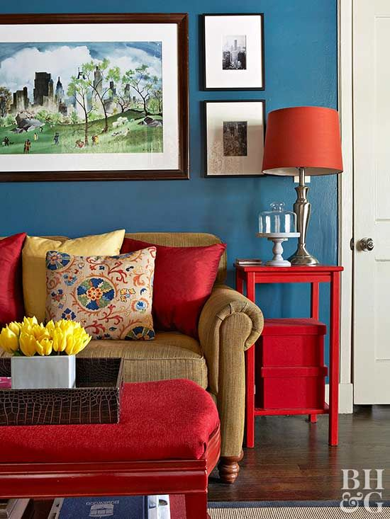 This Living Area Plays To The Three Primary Colors. A Red Ottoman, Side  Table
