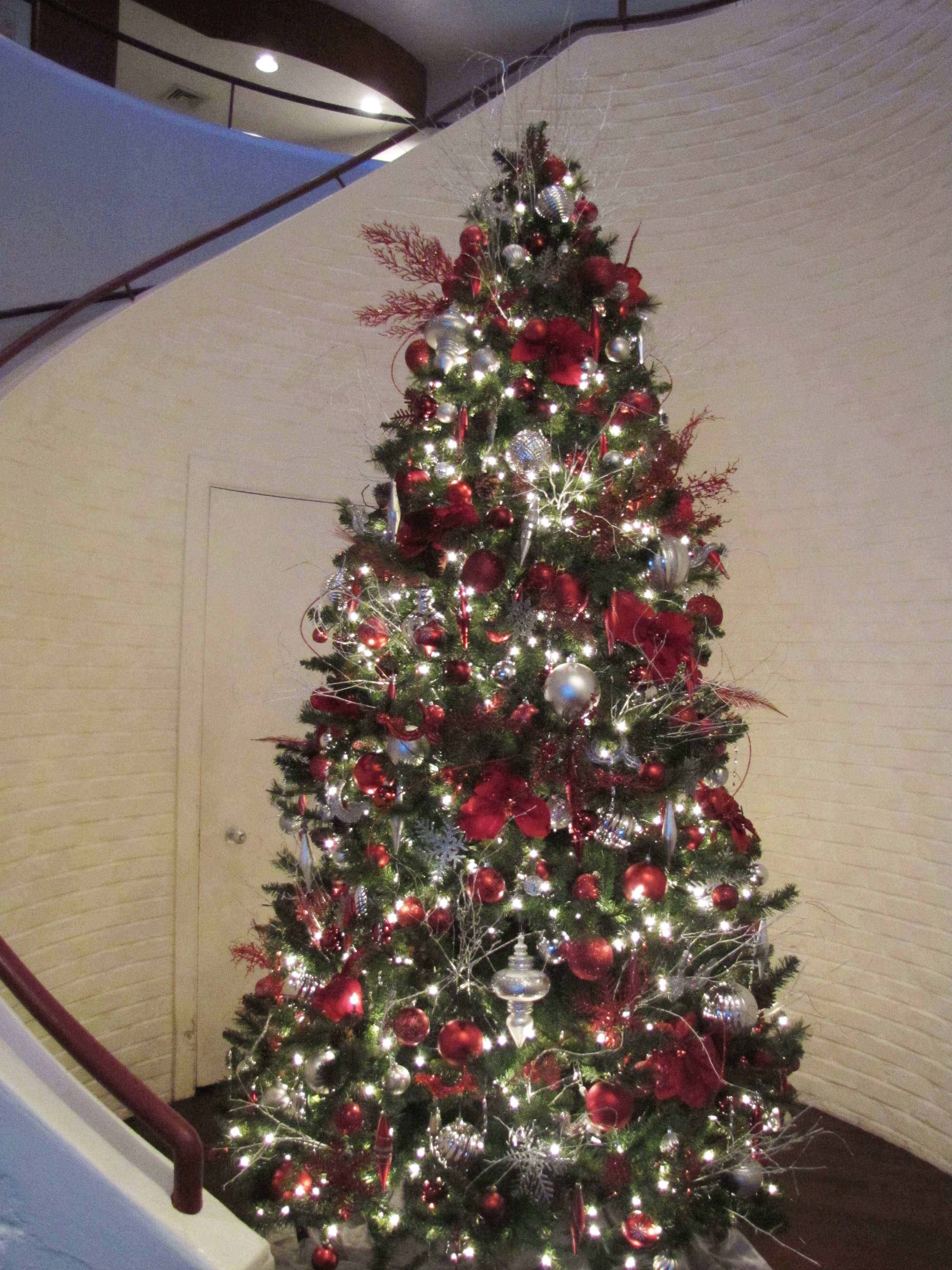 An Elegant Red And Silver Christmas Tree Complements The Red And White Spiral Staircase Christmas Tree Red And Silver Silver Christmas Tree Grey Christmas Tree