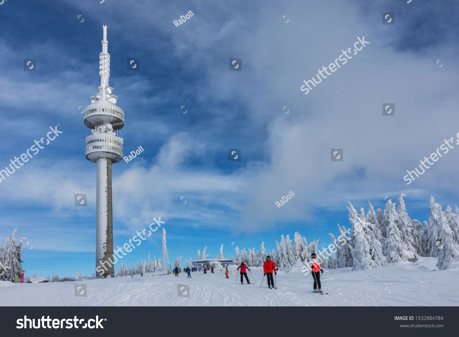 Pamporovo Bulgaria  01312019 Calm sunny morning in ski resort Pamporovo Several people are skiing on white slopes near Snejanka TV tower Sports and recreation concept Sel...