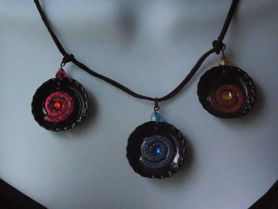 This is a beautiful Black Three Bottle Cap Necklace on a nylon cord. It is embellished with different colors of glitter swirls.