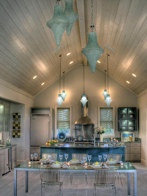 Sky-Blue Frosting--This contemporary kitchen is immediately illuminated by the sky-blue light fixtures hanging from the ceiling. This cool blue hue is carried across the room, from the expansive island and accessories to the lights reflected in the back wall shelves.