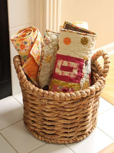 A basket full of lap-sized quilts for keeping guests cozy in your house. What's more welcoming than feeling snuggled up on someone's couch?