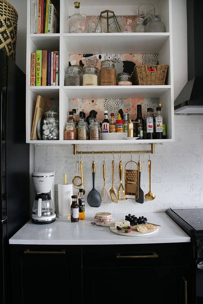 Black And White Kitchen With Marble Tiles And Gold Hanging Utensils