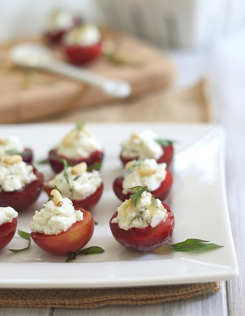 Cheese & Honey Stuffed Plums.  A delicious way to use summer fruit.  Juicy ripe plums (or peaches, nectarines) topped with creamy goat cheese, ribbons of fresh basil, drizzled honey, and a sprinkling of toasted pine nuts. Perfect for a front porch happy hour with friends.